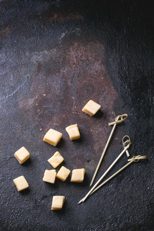 Little cubes of Belgian cheese with cocktail sticks over black background. Top view. Imagens