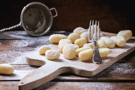 Uncooked homemade potato gnocchi with fork and strainer on vintage cutting board over wooden table with flour. See series Standard-Bild