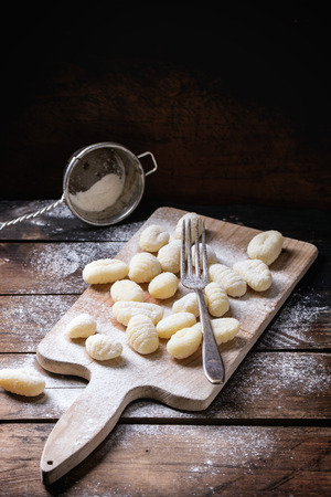 Uncooked homemade potato gnocchi with fork and strainer on vintage cutting board over wooden table with flour. See series Imagens