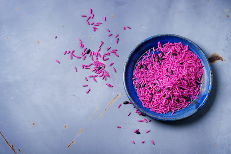 comida japonesa: Arroz rosa sin cocer en la placa de cerámica azul sobre superficie de metal gris. Vista superior.