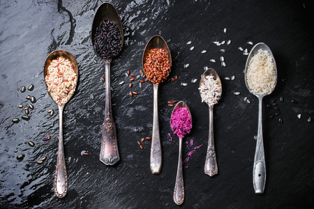 Set of unusual rice in vintage spoons over dark surface. Top view photo
