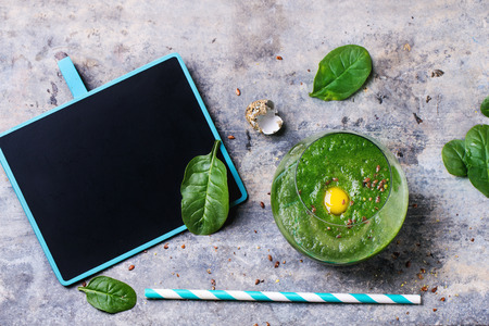 tube top: Glass of green smoothie with quail eggs yolk, served with blank black chalkboard, cocktail tube and baby spinach leaves over tin surface. Top view.