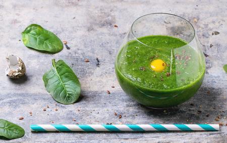 spinach: Vaso de batido de color verde con la yema de codorniz de huevo, servido con tubo de c�ctel y de espinaca hojas sobre la superficie de esta�o.