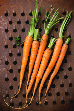 metal grater: Bundle of carrots over old metal grater as background. Top view. Stock Photo