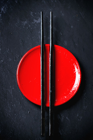 Asian style red plate and black chopsticks over dark background. Top view