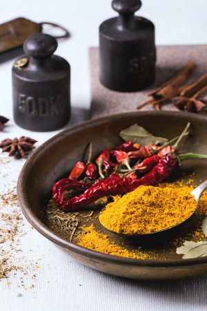 tumeric: Spices tumeric and dry red hot chili peppers on metal plate, served over white tablecloth with vintage weight.
