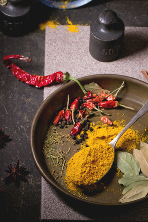 tumeric: Spices tumeric and dry red hot chili peppers on metal plate, served over dark table with vintage weight and blue ceramic plate.