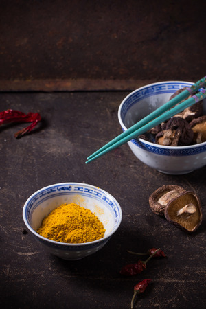tumeric: Tumeric powder and shiitake mushrooms in porcelain bowls, served with red hot chili peppers and turquoise chopsticks over dark table Stock Photo