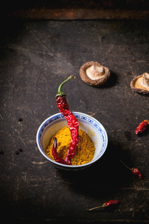 tumeric: Tumeric powder in porcelain bowl, served with shiitake mushrooms and red hot chili peppers over dark table. Stock Photo