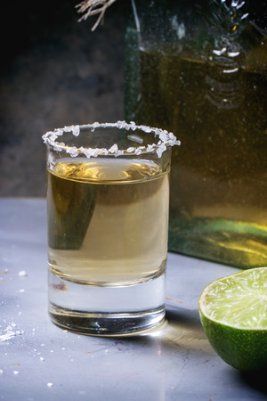 Short of tequila anejo with lime and salt over gray metal table photo