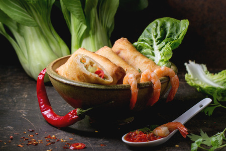 Fried spring rolls with vegetables and shrimps, served in ceramic bowl with spicy sause and Bok Choy over black background.