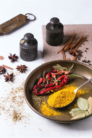 tumeric: Spices tumeric and dry reh hot chili peppers on metal plate, srved over white tablecloth with vintage weight.