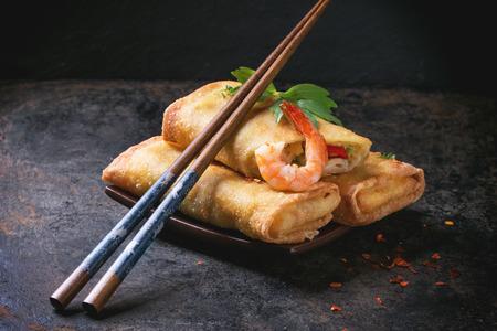 Fried rollos de primavera con verduras y gambas, que se presentan en Squer placa de cerámica con los palillos sobre fondo negro.