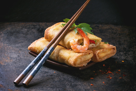 Fried spring rolls with vegetables and shrimps, served on squer ceramic plate with chopsticks over black background.