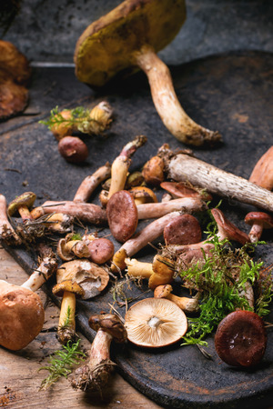 Mix of forest mushrooms on black cutting board over old wooden table. See series photo