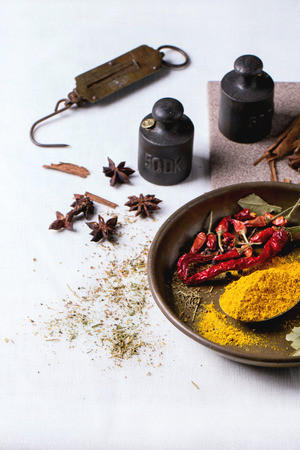 steelyard: Spices tumeric and dry reh hot chili peppers on metal plate, srved over white tablecloth with vintage weight.