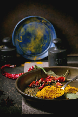 tumeric: Spices tumeric and dry reh hot chili peppers on metal plate, srved over dark table with vintage weight and blue ceramic plate.