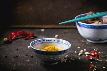 tumeric: Tumeric powder and shiitake mushrooms in porcelain bowls, served with red hot chili peppers and turquoise chopsticks over dark table. See series