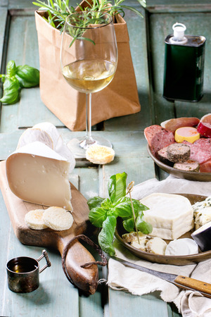 Plates with cheese and sausage variations with fresh basil and glass of white wine over turquoise wooden table. Overhead view. photo