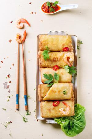 plato de comida: Fried rollos de primavera con verduras y camarones, servido con salsa picante y palillos sobre fondo de madera blanca. Vista superior