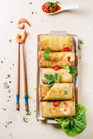 Fried spring rolls with vegetables and shrimps, served with spicy sauce and chopsticks over white wooden background. Top view