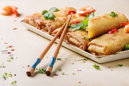 Fried spring rolls with vegetables and shrimps, served with spicy sauce and chopsticks over white wooden background.