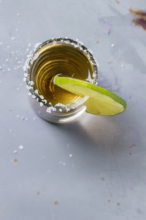 Short of tequila anejo with lime and salt over gray metal table. Overhead view. photo