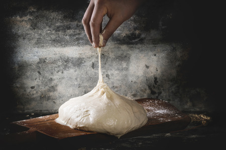 Man's hand pulls the dough for pizza on wooden cutting board over dark kitchen table, powdered with flour