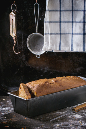 Homemade rye bread in bread pan over kitchen table with towel and vintage stainer and steelyard at background