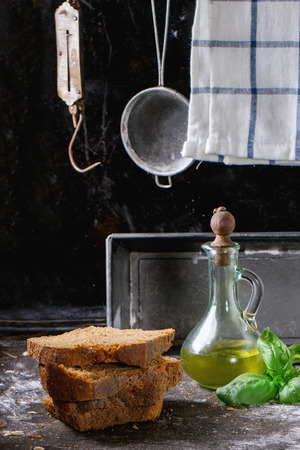 steelyard: Sliced homemade rye bread, battle of olive oil and fresh basil over kitchen table powdered with flour, with towel, bread pan and vintage stainer and steelyard at background Stock Photo