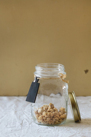 nameplate: Homemade granola in the glass jar with decorate nameplate over white textile in day light