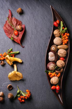 Decoratieve keramische plaat met noten, bessen en paddestoelen op een zwarte achtergrond. Bovenaanzicht