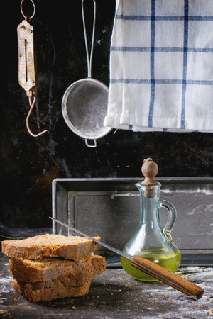 steelyard: Sliсed homemade rye bread and bottle of olive oil over kitchen table powdered with flour, with towel, bread pan and vintage stainer and steelyard at background Stock Photo