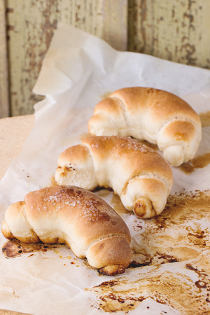 Fresh homemade baked crescent rolls on baking paper and oven stone over light gray tablecloth