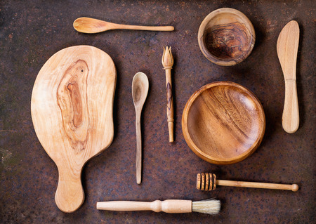 Set of olive wood cookware over brown metal background. Top view photo