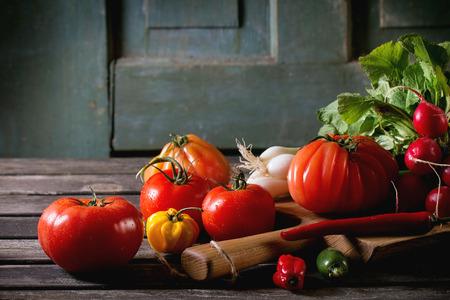 onion: Mont�n de verduras frescas maduras coloridas tomates, chiles, cebolla verde y manojo de r�banos en tajadera de madera sobre la mesa de madera vieja. Ambiente r�stico oscuro