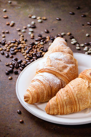 unroasted: Plate with two fresh baked croissants with heap od roasted and  unroasted coffee beans over rusty metal background.