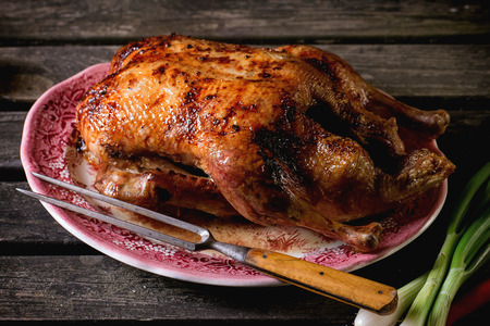 Whole roast honey duck with meat fork in vintage plate, served over old wooden table. Stockfoto