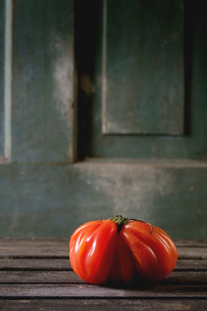 raf: One big red tomato RAF over old wooden table. Dark rustic atmosphere