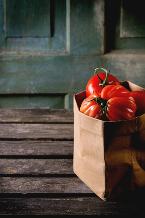 raf: Heap of big red tomatoes RAF in paper bag over old wooden table. Dark rustic atmosphere Stock Photo