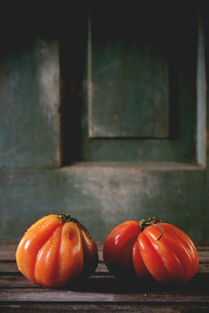raf: Two big red tomatoes RAF over old wooden table. Dark rustic atmosphere Stock Photo