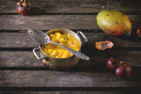 mango fruta: Haciendo chutney de mango o mermelada en recipiente de aluminio de la vendimia sobre vieja mesa con mango y mangost�n. Ambiente r�stico oscuro