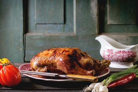 PATO: Todo el pato asado con miel tenedor de carne en la placa de la vendimia, que se sirve con verduras frescas y salsera de porcelana sobre la mesa de madera vieja.