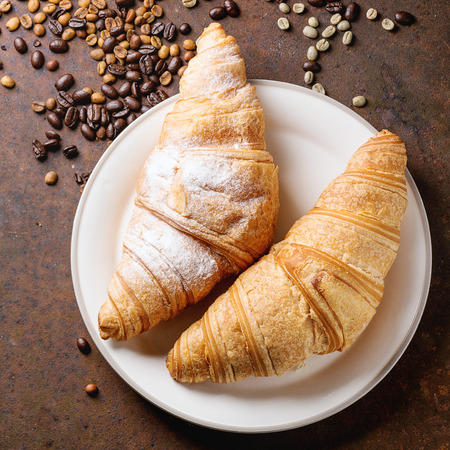 unroasted: Plate with two fresh baked croissants with heap od roasted and  unroasted coffee beans over rusty metal background. Square image