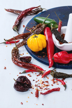 dryed: Assortment of fresh, dryed and flakes hot chili peppers with white ceramic mortar on dark blue cutting board over light blue wooden background