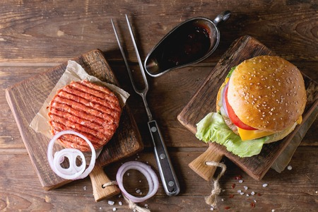 Fresh homemade burger on little cutting board and raw cutlet and sliced onion, served with ketchup sauce and meat fork over wooden table. Dark rustic style. Top view