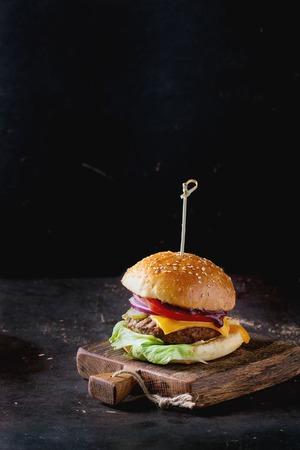 comida gourmet: Hamburguesa casera fresca en pequeña tabla de cortar de madera sobre fondo oscuro.