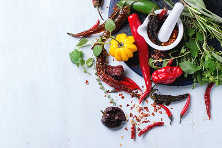Assortment of fresh, dryed and flakes hot chili peppers and fresh herbs with white ceramic mortar on dark blue cutting board over light blue wooden background. Top view