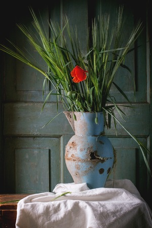 Bouquet of yang green barley with blooming red poppy flower in old metal vase on wooden table. Dark rustic atmosphere