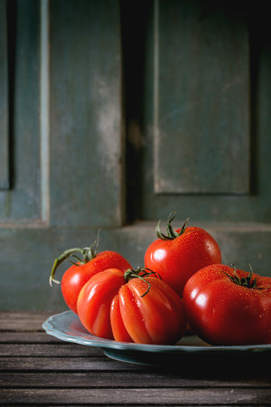 raf: Heap of big red tomatoes RAF on turquoise plate over old wooden table. Dark rustic atmosphere Stock Photo